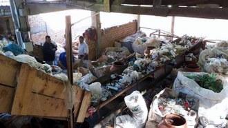 Foto aberta, em um local amplo, porém fechado, como um galpão. Há sacos de resíduos sólidos distribuídos em toda a área da foto. Há uma esteira no centro da foto, carregando resíduos. Há duas pessoas ao lado da esteira, em pé.