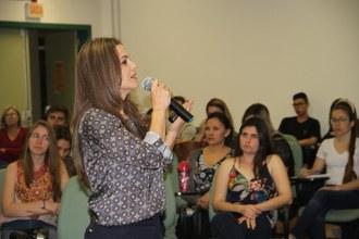 Mulher de lado falando ao microfone