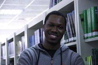 Em plano médio, foto mostra Bachelor sorrindo, com o fundo das prateleiras da biblioteca