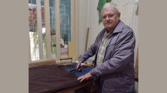 Na foto, o Sr. Simon aparece de lado, em pé, em frente a um balcão, cortando uma peça de roupa