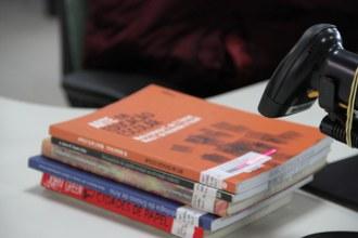 Uma pilha de livros está em cima de uma mesa e, em frente, o leitor de código de barras, cuja luz está apontada para o código fixado em um dos livros