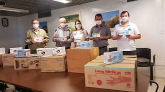 Atrás de uma mesa com caixas de luvas e máscaras, cinco pessoas estão em pé, de máscaras e segurando caixas de luvas