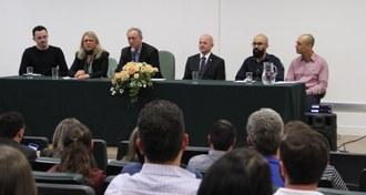 Em primeiro plano, pessoas sentadas de costas olhando para a mesa de honra. Na mesa de honra, seis pessoas estão sentadas lado a lado