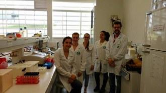 Quatro mulheres e um homem estão de jaleco branco, em um laboratório