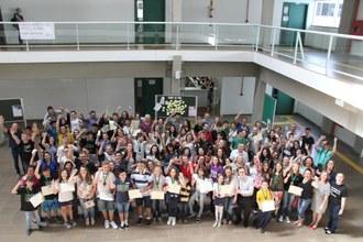 Pais, estudantes, professores e gestores estão em pé, no hall do Bloco A, comemorando a premiação na OMOC.