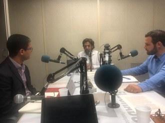 imagem de dois professores sendo entrevistados numa mesa de rádio