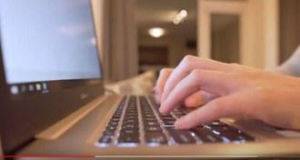 Numa imagem bem fechada aparecem as mãos de uma pessoa digitando em um teclado de notebook.