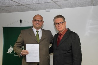 Foto do novo diretor segurando o termo de posse, abraçado ao reitor da universidade