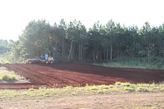 Na imagem a máquina está fazendo a terraplanagem no terreno destinado ao campo de futebol.