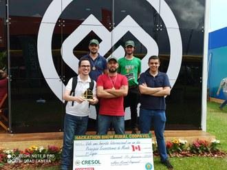 Na imagem os cinco integrantes da equipe posam com um vale em tamanho gigante, contendo a descrição do prêmio recebido. Um estudante segura nas mãos o troféu da equipe.