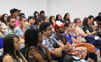 Na imagem, vários estudantes estão sentados em cadeiras enfileiradas observando algo a sua frente.