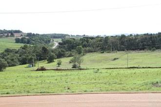 Na imagem em plano aberto, uma máquina está fazendo terraplanagem em terreno onde será instalada a Estação de Aquicultura.