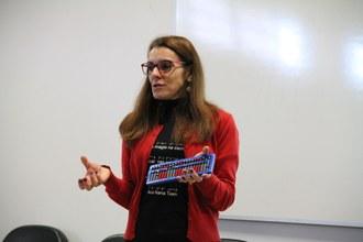 Na imagem a palestrante Maristela Vanin Pinto está no palco do auditório e faz demonstração usando o Sorobã, que está em sua mão esqueda.