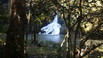 Foto em plano aberto. No primeiro plano observam-se árvores e ao fundo uma cachoeira e um pequeno lago.