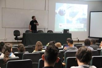 Estudantes sentados em auditório assistem apresentação de palestrante que está no palco. Ao lado esquerdo a imagem de um peixe é projetada no telão.