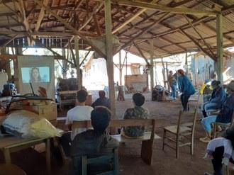 Foto mostra um barracão de madeira onde um grupo de pessoas está sentado de frente para uma tela, na qual é projetado um vídeo. As pessoas mantém distância uma das outras.