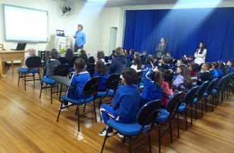 Dentro de uma sala de aula as crianças estão sentadas assistindo apresentação do professor.