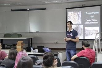 Na foto uma pessoa está em pé, em frente ao público. Ao fundo observa-se os slides que auxíliam na apresentação da palestra.