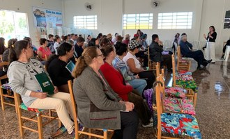 Na imagem várias pessoas estão sentadas assistindo palestra que ocorro em auditório.