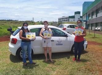 No centro da imagem três mulheres seguram livros, ao fundo dois carros e os prédios da UFFS - Campus Laranjeiras do Sul.