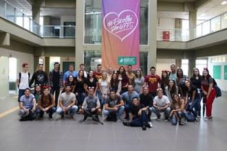 Foto em plano aberto dos novos alunos e calouros lado a lado posando para a foto no hall de entrada do bloco A