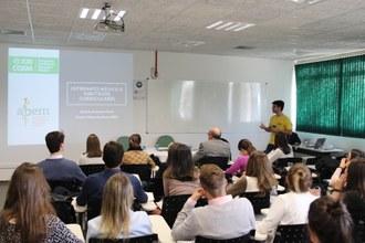 Foto em plano aberto mostrando palestrante ao fundo de frente para o público que está sentado em sala de aula