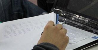 Foto, em plano fechado, de uma mão segurando um caderno e uma caneta
