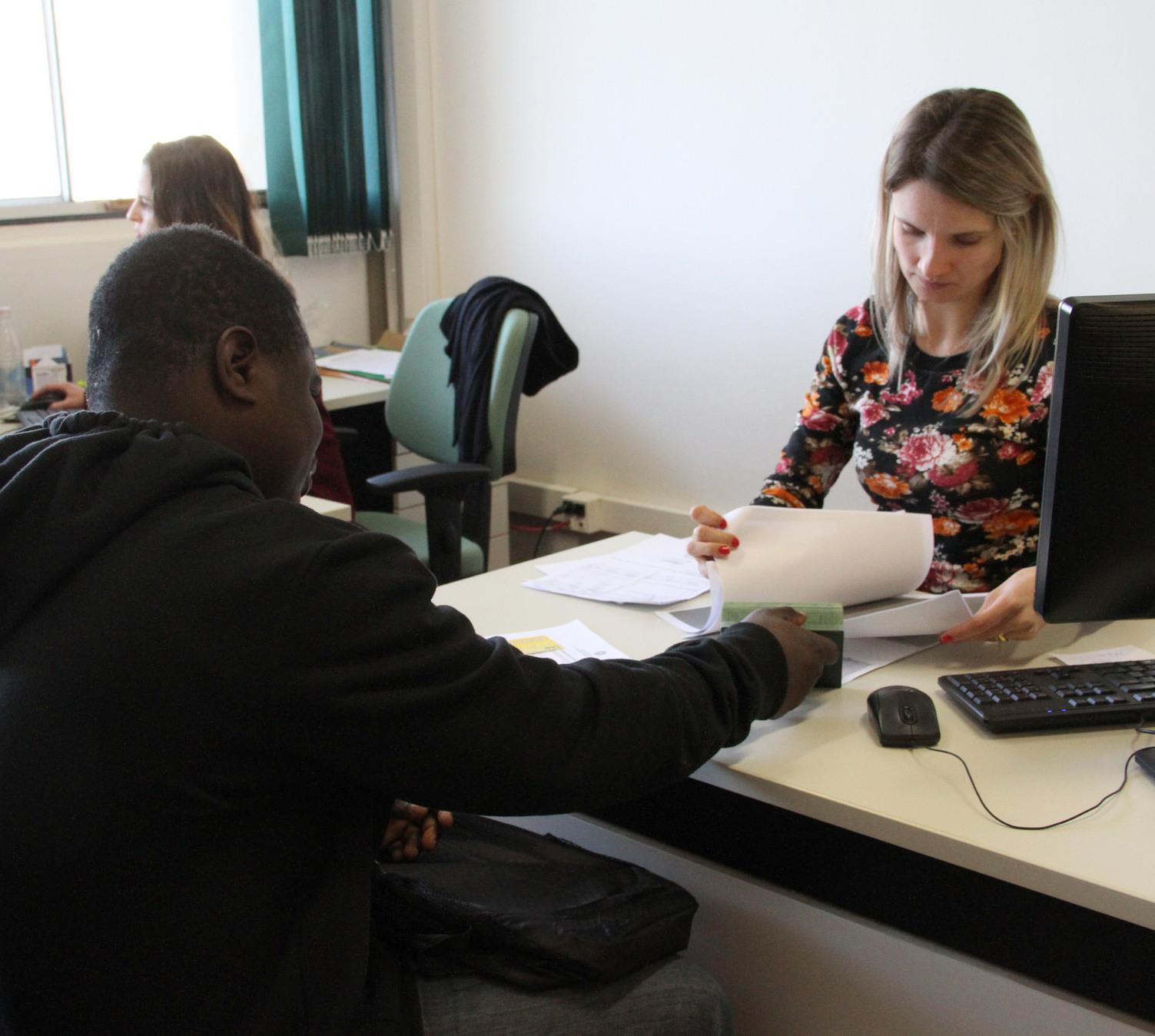 Duas pessoas sentadas, uma de cada lado de uma mesa durante um atendimento na assistência estudantil da UFFS