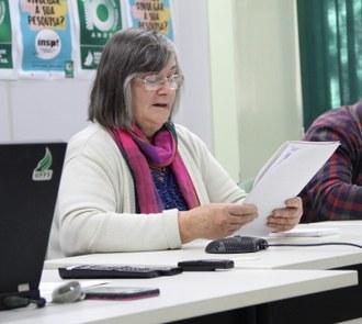 Foto em plano fechado de uma mulher sentada, segurando um documento e realizando a leitura dele.