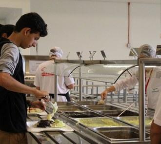 Pessoas ao redor de balcão servindo refeições