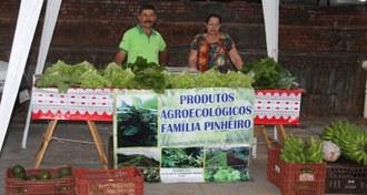 Duas pessoas sob uma barraca oferecendo produtos agroecológicos