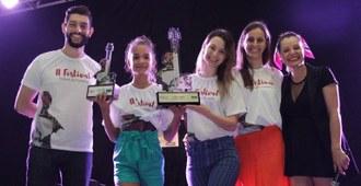 Cinco pessoas posam para foto, duas delas seguram troféus.