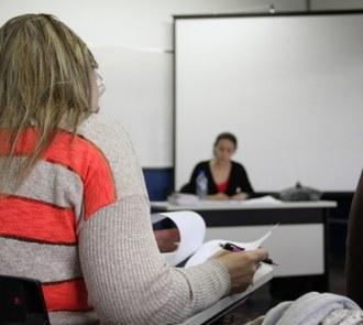 Aluna, sentada em uma cadeira, de costas para a câmera, escreve em seu caderno sob uma carteira escolar