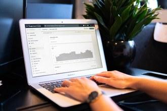 Imagem de um notebook aberto com duas mãos sobre o teclado e ao fundo um vaso de planta na cor preta