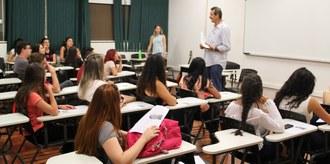 Alunos em sala de aula, sentados em suas carteiras, observam um professor