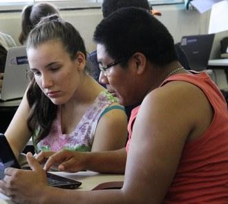 Dois alunos, em uma sala de aula, olham para um notebook